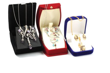 Golden jewelry sets inside open boxes, on white Stock Photo - 7564450