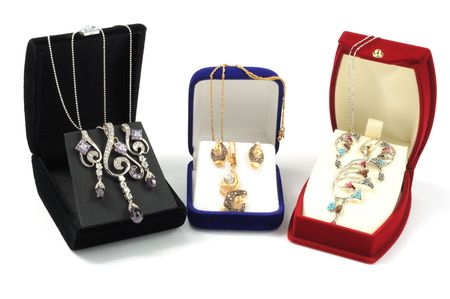 Gold jewelry sets in open boxes, on white background photo