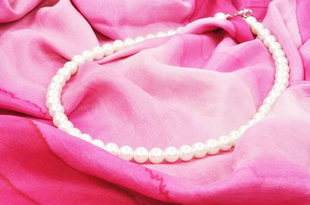 White pearl necklace laying on pink silk, close up photo