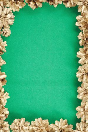 Christmas green background with gold cones frame photo