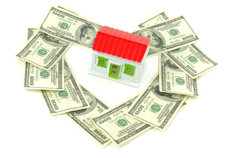 downpayment: Toy house with hundreds dollars around it, over white background