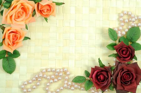 Frame from roses and pearls on wooden background photo