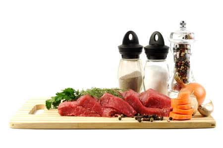 Fresh raw meat with some spice on a plate ,  on white a white background photo