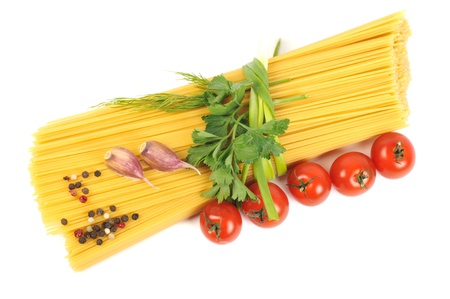 Bunch of raw pasta (spaghetti) tied with fresh green spice , tomato and garlic,  with copy space photo