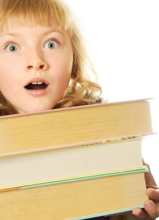 Surprised girl with big books, isolated on white photo