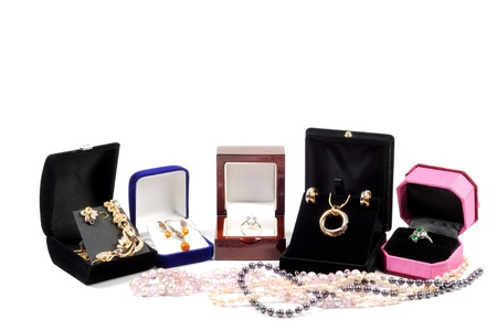 necklase: An open jewlery boxes with gold and platinum  jewelry sets on a white background