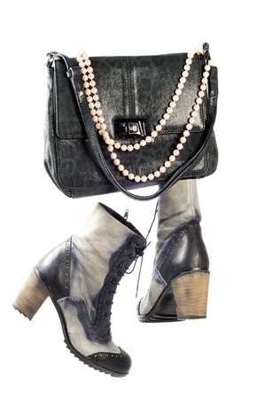 Pair of modern leather boots and woman silver purse  with pearl necklace over white background photo