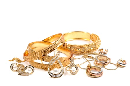 Golden bracelets and jewelry sets, over white photo