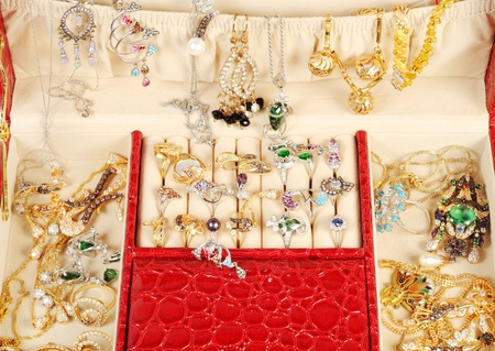 An open jewlery box with gold and platinum  jewelry and accessory close up photo