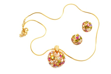 Golden earrings and necklace with colorful gems, over white