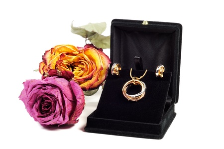 An open jewlery box with gold and platinum  jewelry set with dry roses photo