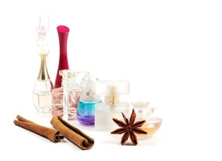 Las botellas de perfumes, an�s y canela, sobre fondo blanco enfoque selectivo en el frente Foto de archivo - 13404875