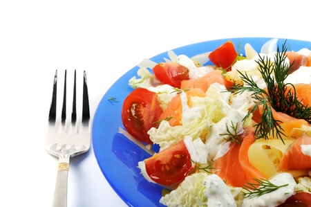 Fresh ceasar salad in a blue plate and fork, on white background photo