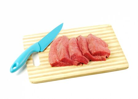 Fresh raw meat and blue knife, on a white background photo