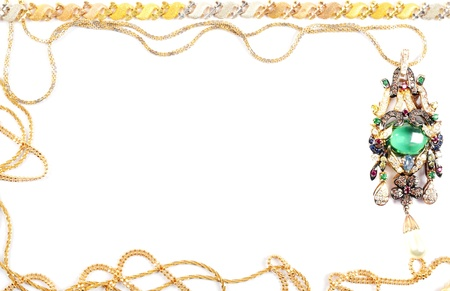 Golden chains and necklace with emerald and gems, fraim,over white Stock Photo - 13727542