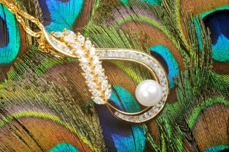 Golden necklacee with colorful gems and pearl on the peacook feather