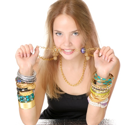 Teen girl with lot  bracelets and necklace in her mouth photo
