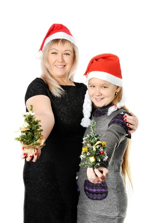 Mother hugging her teen doughter, on a white background, with Santa hap on Stock Photo - 22079156