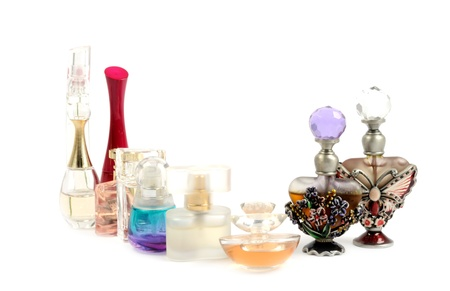 Bottles of essential oil and perfumes, over white background. Selective focus on front botle