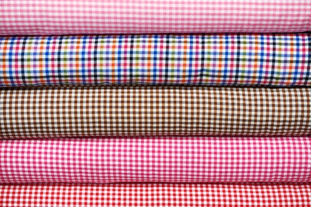 textil: Colorful cotton fabric rolls in the shop shelf, closeup