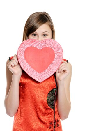 ragazza innamorata: Happy teenager girl  holding red heart, over white