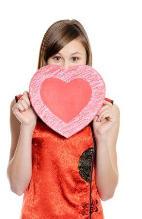 ragazza innamorata: Ragazza felice dell'adolescente che tiene cuore rosso, su bianco