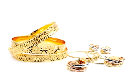 Golden bracelets and jewelry sets, over white