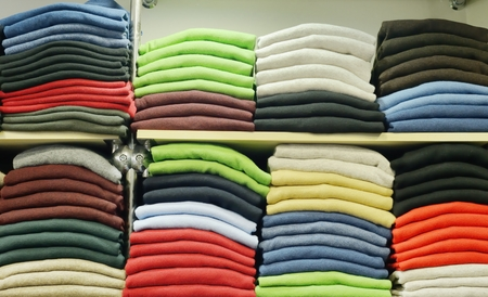 shelfs: Piles of t-shirts on a shelfs, inside a show room