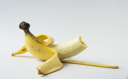 Peel banana and half biten on the white background