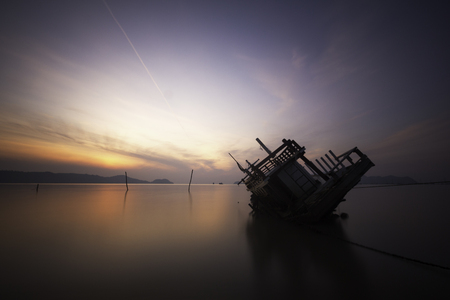 A sinking boat in the sea during sunrise.
