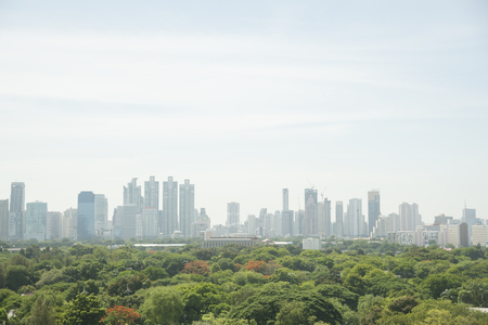 lumpini: Green trees in Lumpini park and buildings in the city of Bangkok Stock Photo