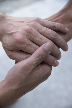 A man holding another mans hand for sympathy 版權商用圖片