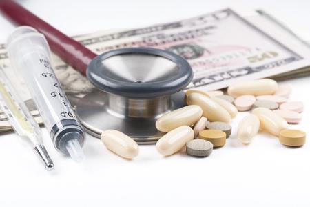 Medications, syringe, thermometer, stethoscope, dollar bills  on the white background