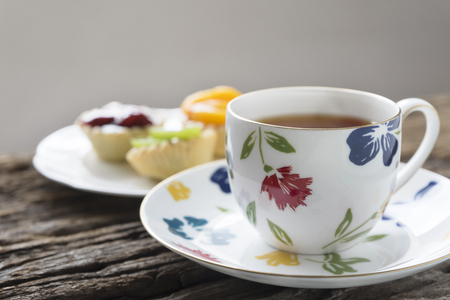A porcelain cup of tea and delicious fruit tarts on the wood table