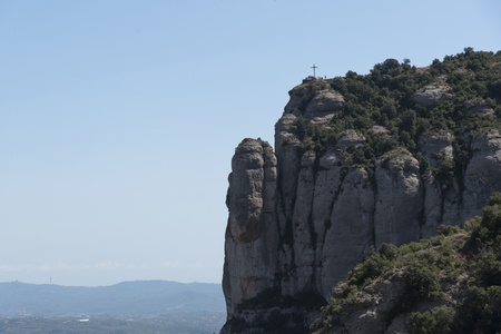 A cross on the top of montserrat in a blue sky day