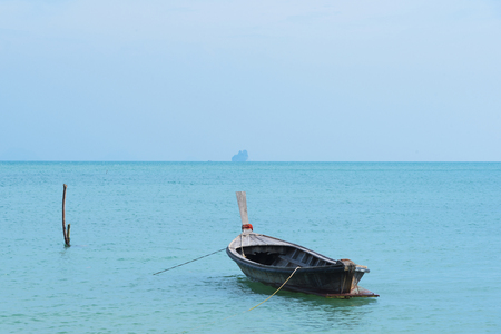 A wooden boat in a beautiful blue sea and blue sky