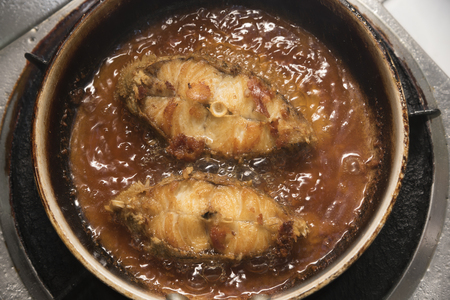 Cooking fried grouper fish in a hot pan on gas stoven