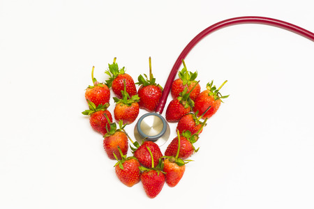 Concept of strawberries in heart shape and a red stethoscope on white background