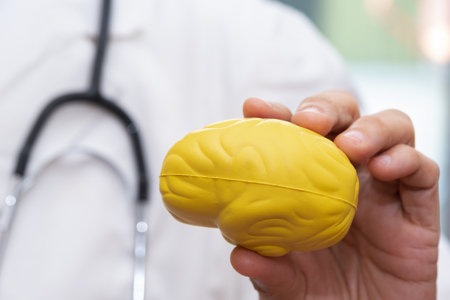 Doctor using finger to hold a yellow brain model