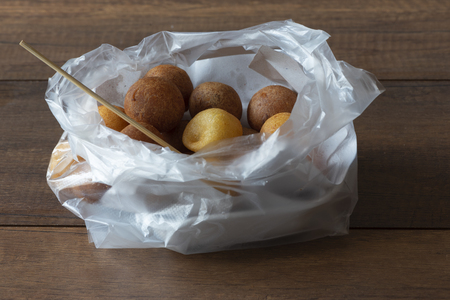 Delicious Thai fried sweet potato balls in plastic bag with on wooden table