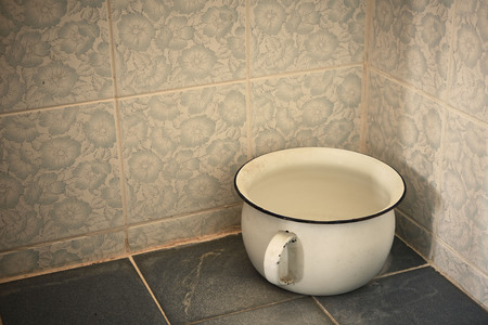 An old white urine pot in the bathroom