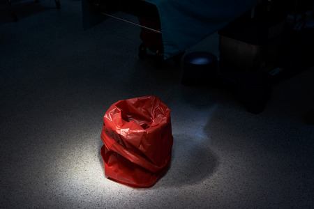 Empty red bin for garbage in the operating room
