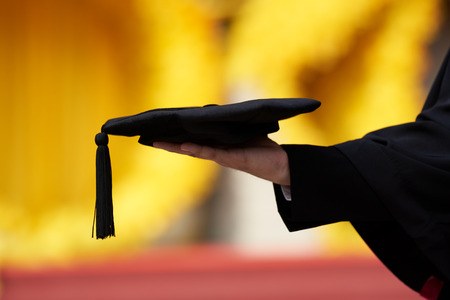 A young graduate hand holding a black graduate cap on yellow background Banco de Imagens