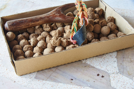 A wooden slingshot and many clay balls in paper box Foto de archivo