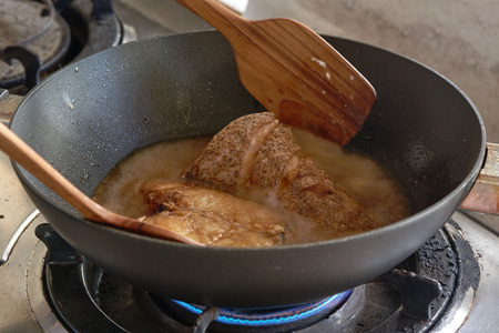 Using wooden turner for cooking raw grouper fish in the pan with gas stove in the kitchen