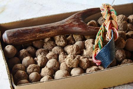 Vista cercana de un tirachinas de madera y muchas bolas de arcilla en caja de papel Foto de archivo