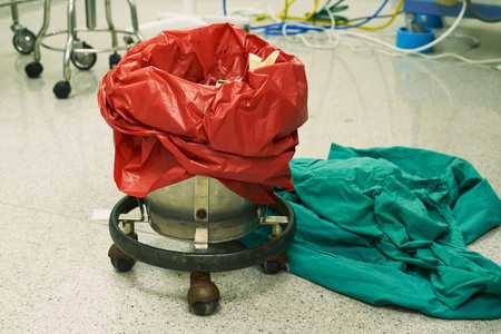 Used surgical gloves in a red garbage bin for biohazard disposal in operating room. Green clothes on the floor. 写真素材
