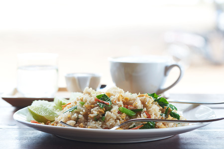 A plate of delicious fried rice and a tasty cup of latte coffee on wooden table