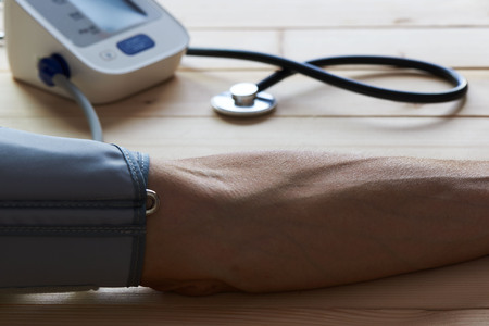 Close-up view of measure blood pressure of a man in clinic by digital sphygmomanometer.