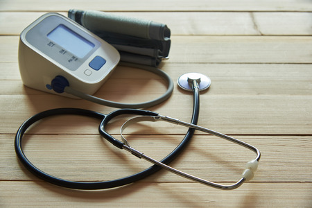 A black stethoscope and digital sphygmomanometer on wooden background